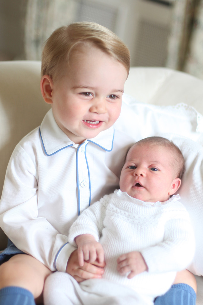 Prince George holding Princess Charlotte. While she's not wearing an infant gown like previous generations, she still has a peter pan collar and a classic sweater, both in traditional white.