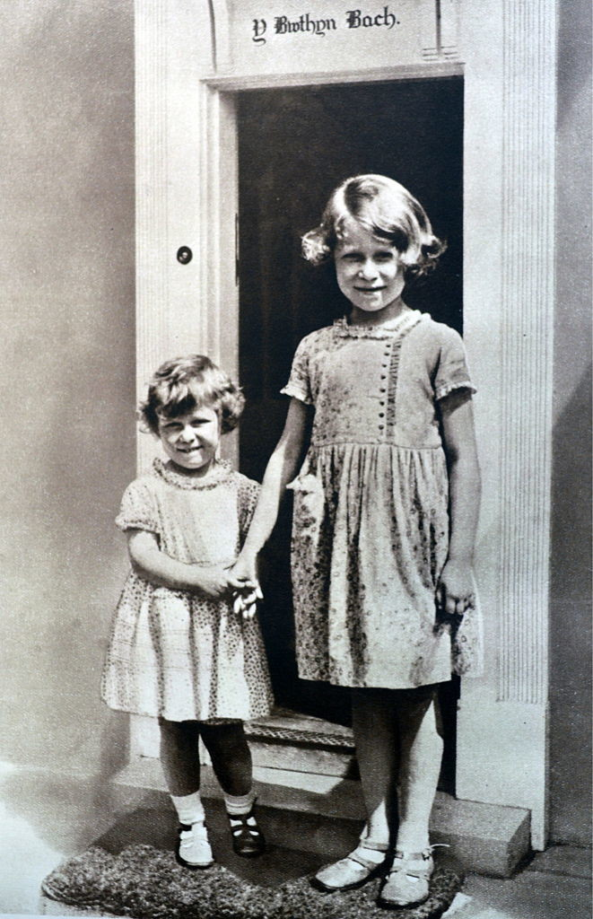 Princess Elizabeth (right) and Princess Margaret (left). Both girls are wearing floral dresses with Peter Pan collars, classic shoes and socks, and hair kept short.