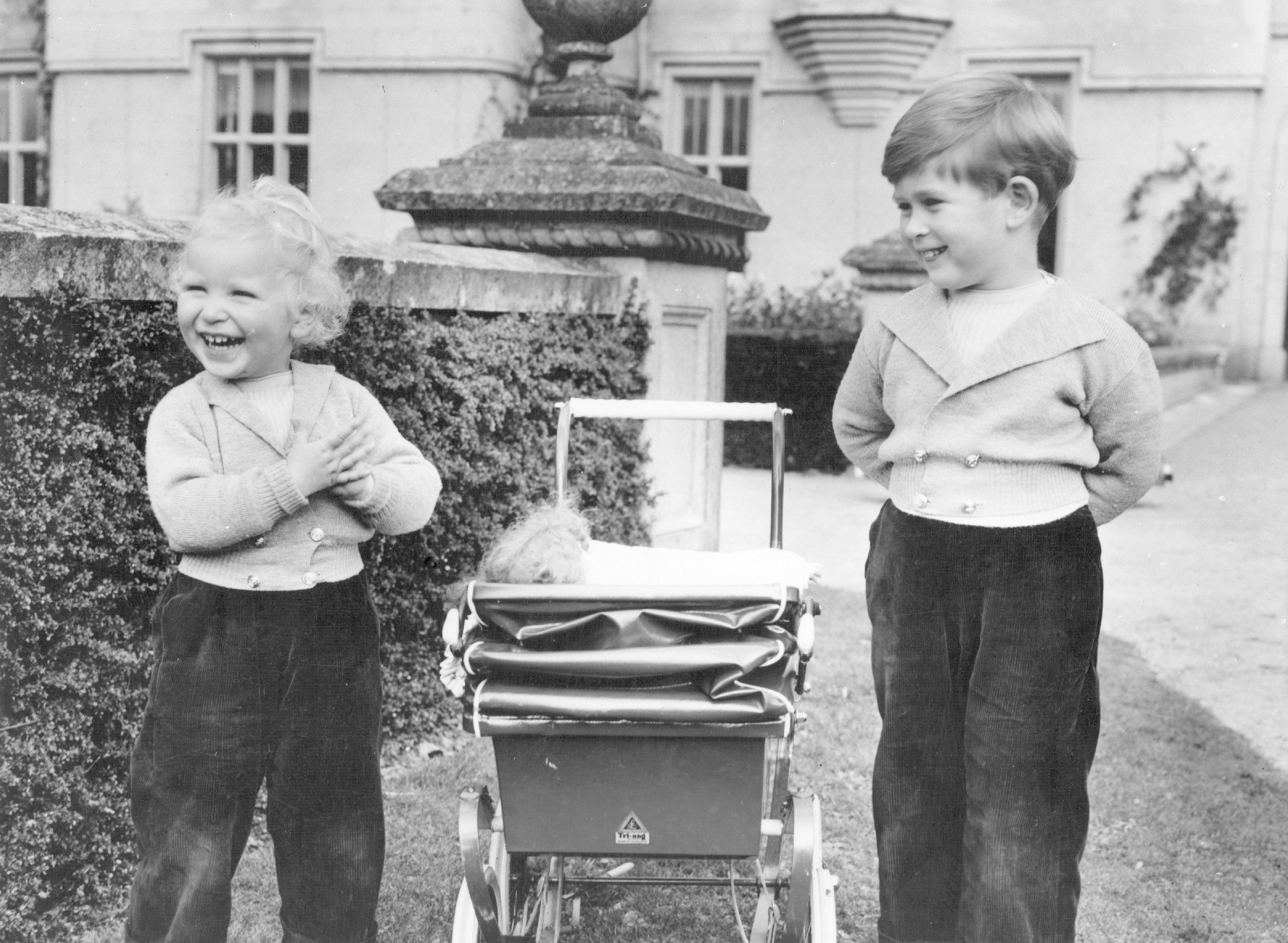 Princess Anne and Prince Charles playing outdoors in 1952. They're both wearing trousers and blazers for informal play.