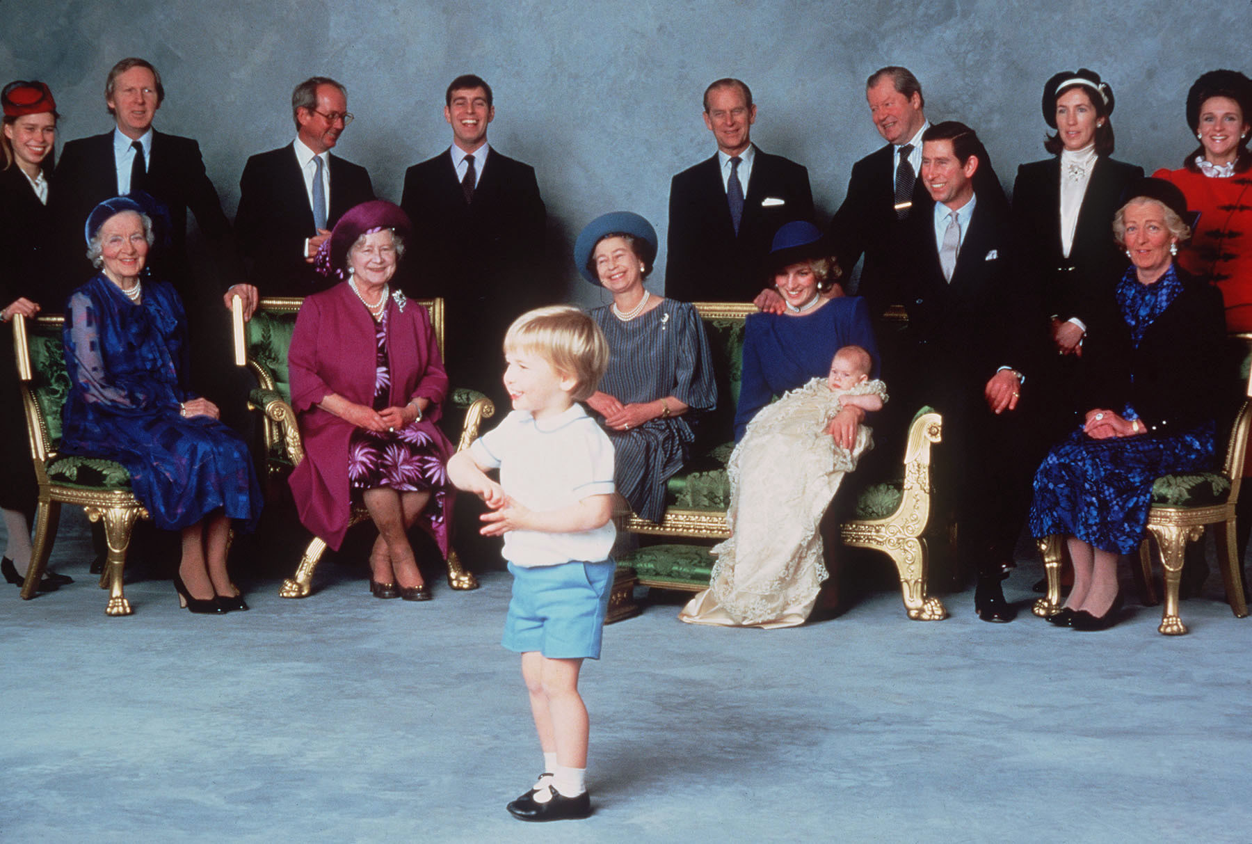 The royal family at the Christening of Prince Harry with Prince William in the foreground. Note the heirloom christening gown on Prince Harry.